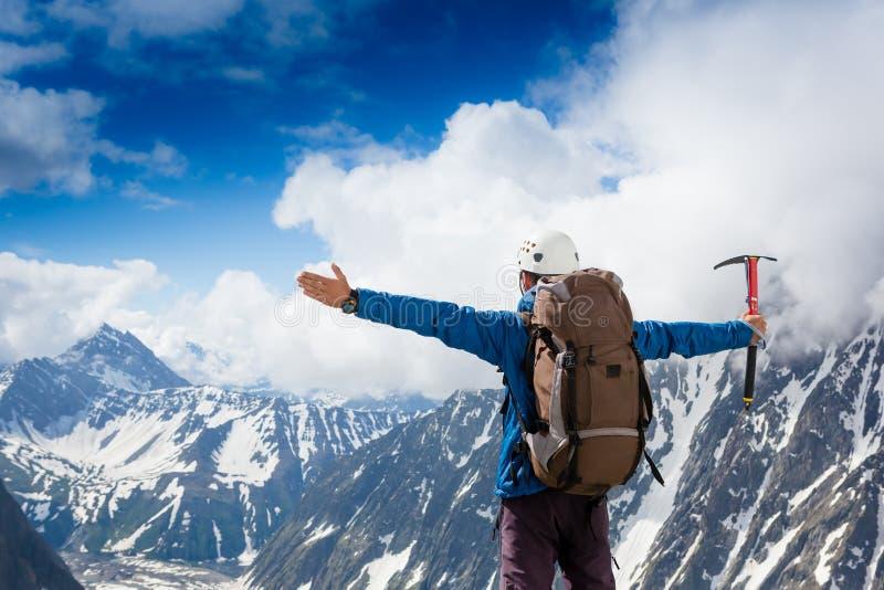 远足者在一个岩石顶部用他的被举的手 库存图片