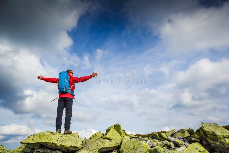远足者在与背包的一个岩石顶部享受晴天 免版税图库摄影