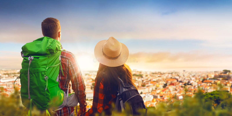 远足者在从山的上面的都市风景看 免版税库存图片