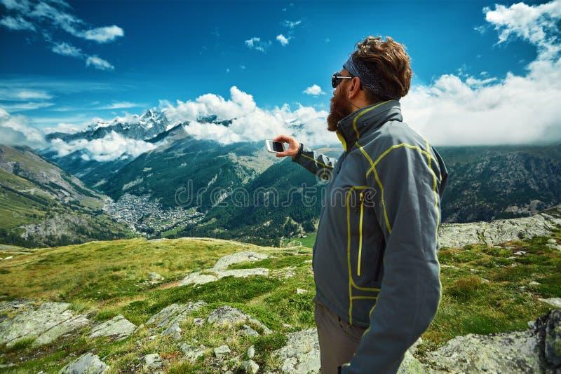 远足者在做selfie的通行证顶部反对高山山 免版税库存照片