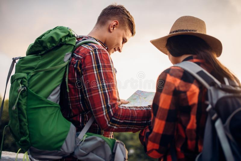 远足者在地图,游览看在旅游镇 免版税库存照片