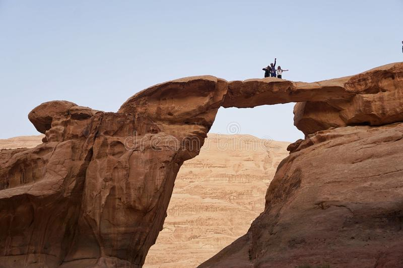 远足者在沙漠庆祝的一座山顶部 库存照片
