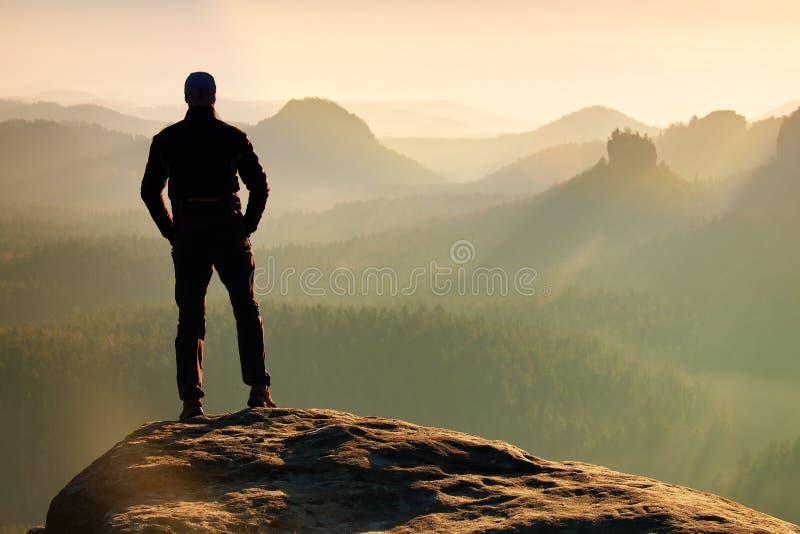 远足者在砂岩岩石峰顶站立在岩石帝国停放并且观看在有薄雾和有雾的早晨谷对太阳 免版税库存图片