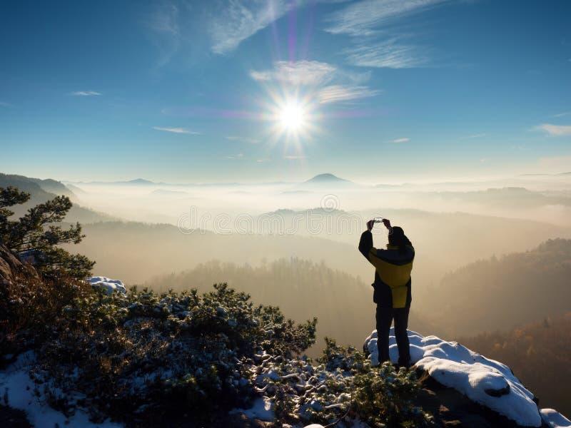 远足者在头上的举行电话,拍有薄雾的冬天风景的照片 免版税库存图片