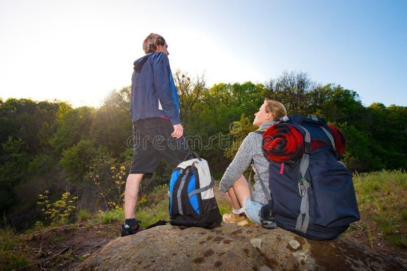 远足者夫妇有休息在他们的w的日落的背包的 免版税库存图片