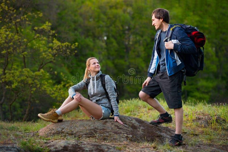 远足者夫妇有休息在途中的森林里的背包的 库存图片