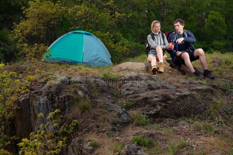 远足者夫妇有杯子的在帐篷附近的热的茶在森林里 库存图片