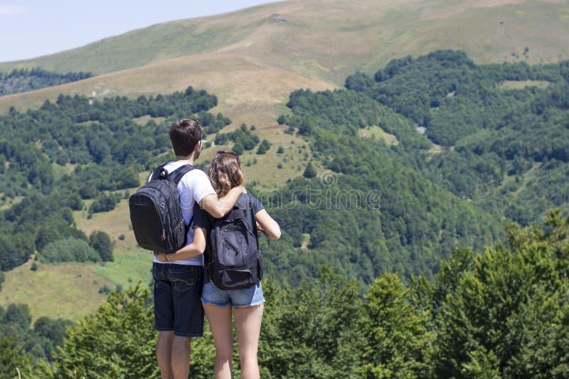 远足者夫妇有站立在观点和enjoyi的背包的 免版税图库摄影