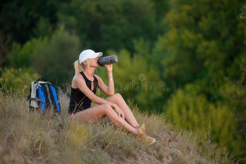 远足者妇女休息的饮用水,旅行在森林里 库存照片