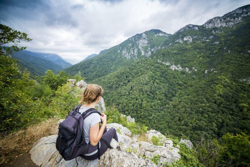 远足者少妇坐与背包的一个岩石 免版税库存图片