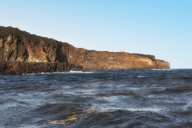 远足者排行峭壁,观看熔岩流到海洋里 免版税库存图片