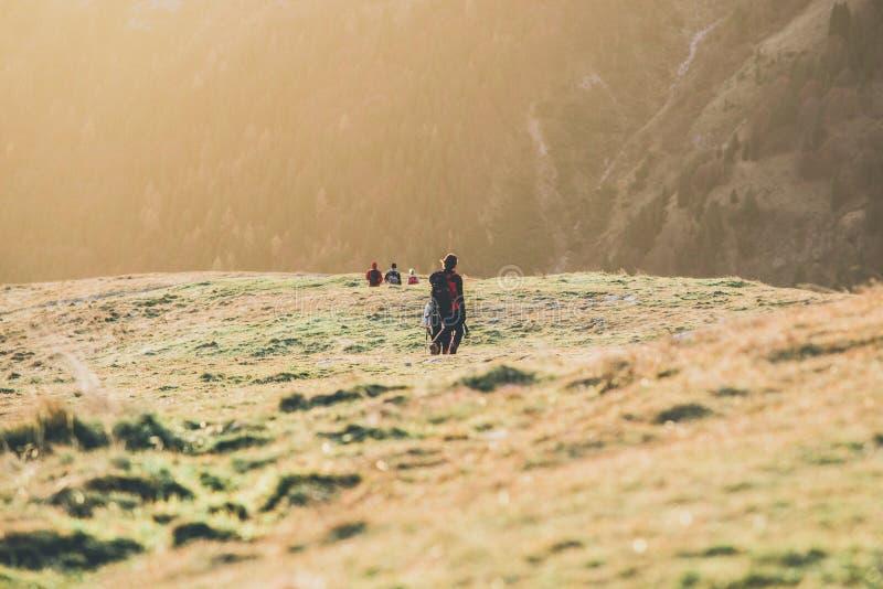 远足者支持在家在日落室外活动春天心情-成为不饱和的样式图象 库存照片