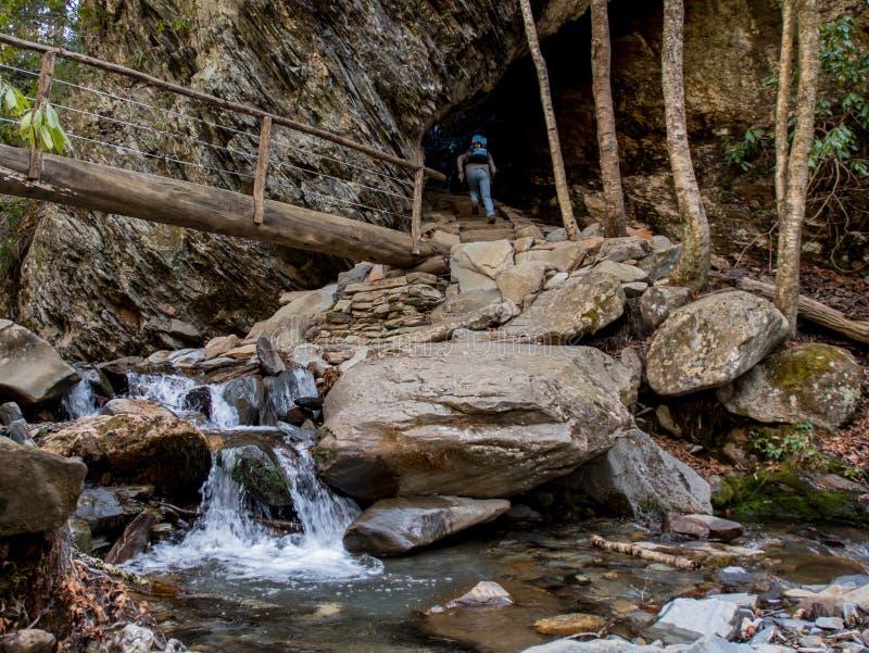 远足者通过曲拱岩石攀登台阶 库存图片