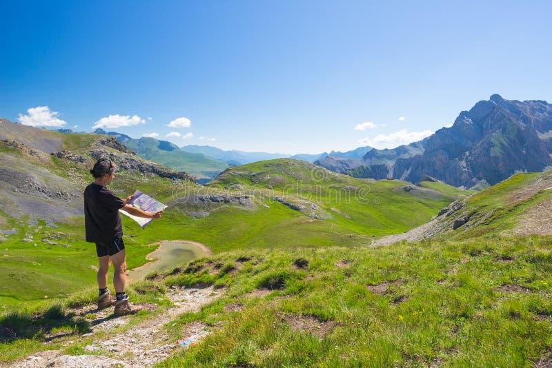 远足者读书迁徙的地图,当休息在全景山斑点时 户外活动、夏天冒险和探险在 库存照片