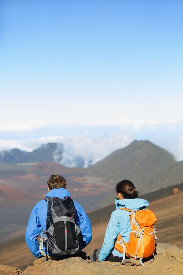 远足者-远足坐的人们享受山顶上面 免版税图库摄影