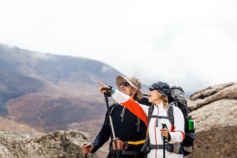 远足走在山的夫妇 免版税库存照片