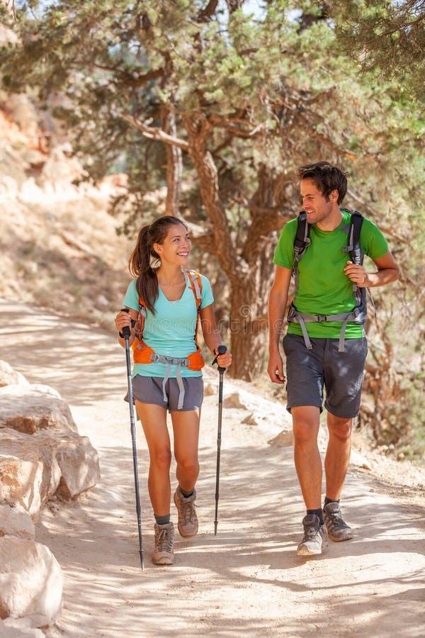 远足足迹步行艰苦跋涉的与远足杆走在大峡谷的徒步旅行者夫妇  年轻亚裔女孩,白种人人,多种族 图库摄影