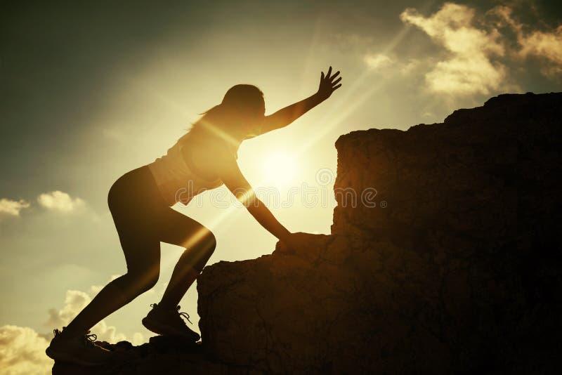 远足运动员妇女请求帮忙在山顶 库存图片