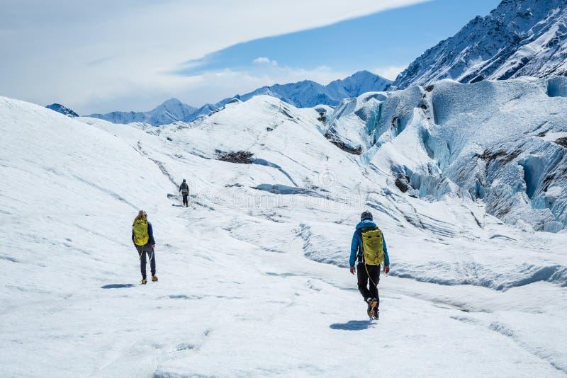 远足马塔努斯卡冰川的三个指南 迁徙在谷冰川的白色冰在遥远的阿拉斯加 免版税库存照片