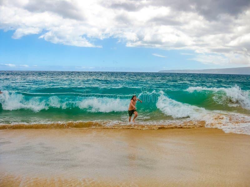 远离波浪的男孩奔跑 库存照片