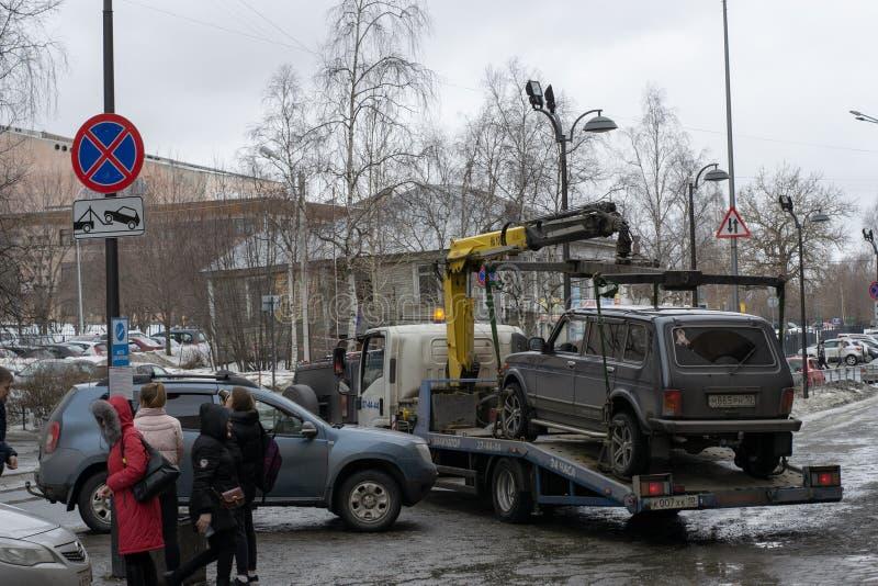 违犯了本市通话业务和停放的法律非法地停放的汽车的拖曳  免版税库存图片