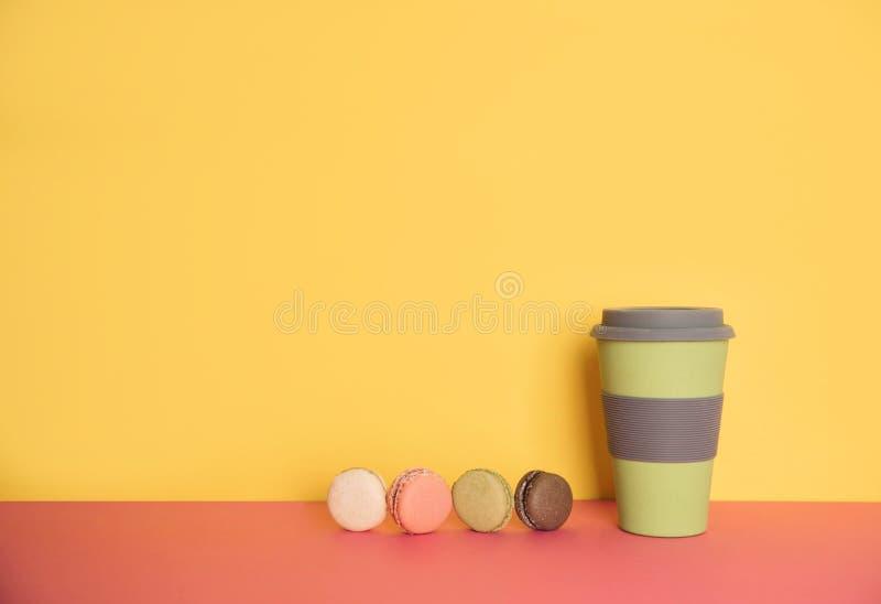 连同的咖啡在黄色和桃红色背景的macaron 库存图片