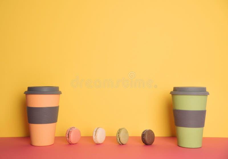 连同的咖啡在黄色和桃红色背景的macaron 库存照片