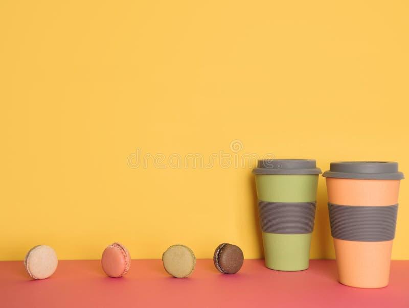 连同的咖啡在黄色和桃红色背景的macaron 图库摄影