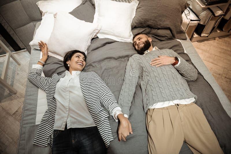 连接他们的手的放光的快乐的夫妇,当说谎时 图库摄影