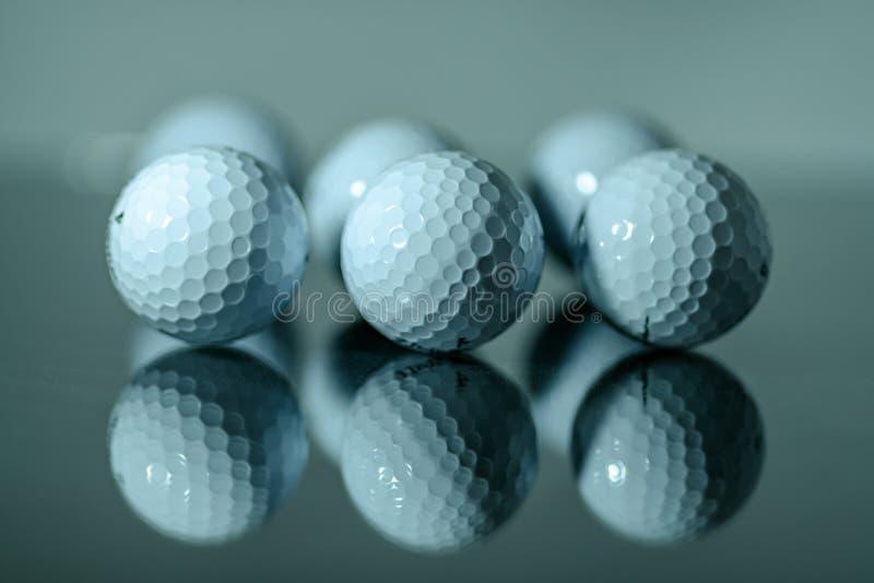 连续反射在镜子的白色高尔夫球 免版税库存照片