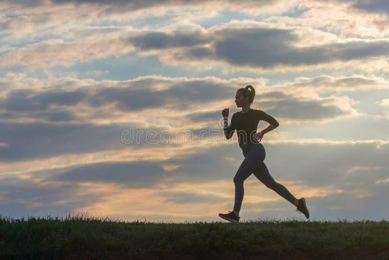 连续妇女早晨锻炼 母赛跑者 跑步在日出期间 锻炼在公园 运动的年轻女人 健身模型 图库摄影