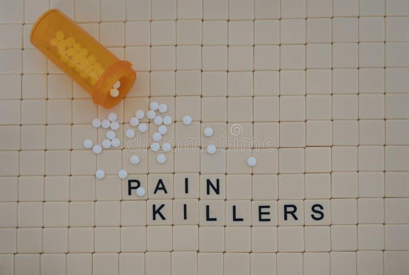 连续拼写止痛药和白色片剂在瓦片的瓦片 库存照片