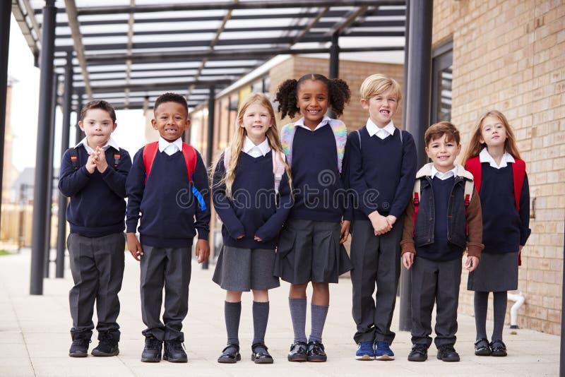 连续站立在一个走道的小学孩子他们的学校外,微笑对照相机,低角度 库存图片