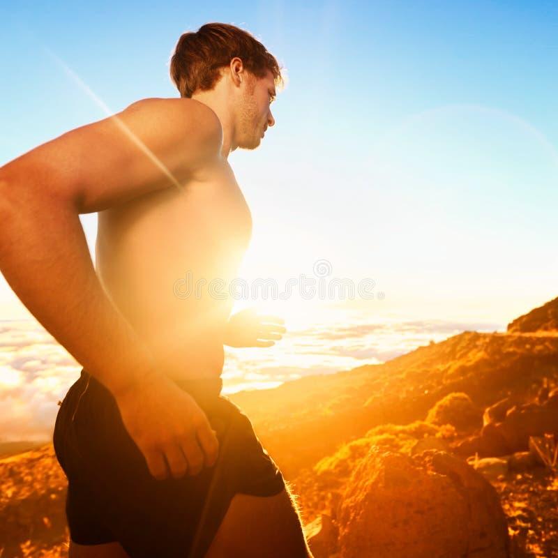 连续人民-日落的男性赛跑者在山 图库摄影