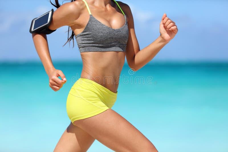 连续健身妇女赛跑者佩带的电话臂章 免版税库存照片