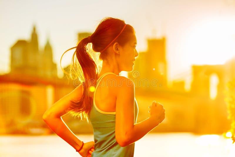 连续在纽约日落的妇女亚洲赛跑者 免版税图库摄影