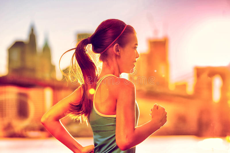 连续在纽约日落的妇女亚洲赛跑者 库存图片