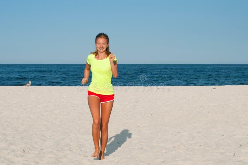 连续妇女 跑步在海滩的室外锻炼期间的母赛跑者 图库摄影