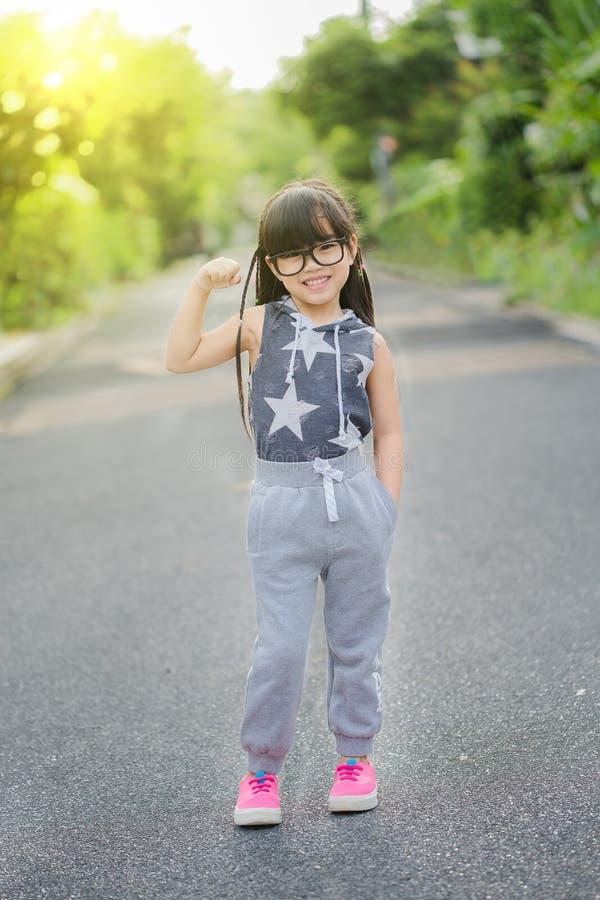 连续孩子在公园 在运动的连续衣裳的亚洲体育健身模型 免版税库存图片
