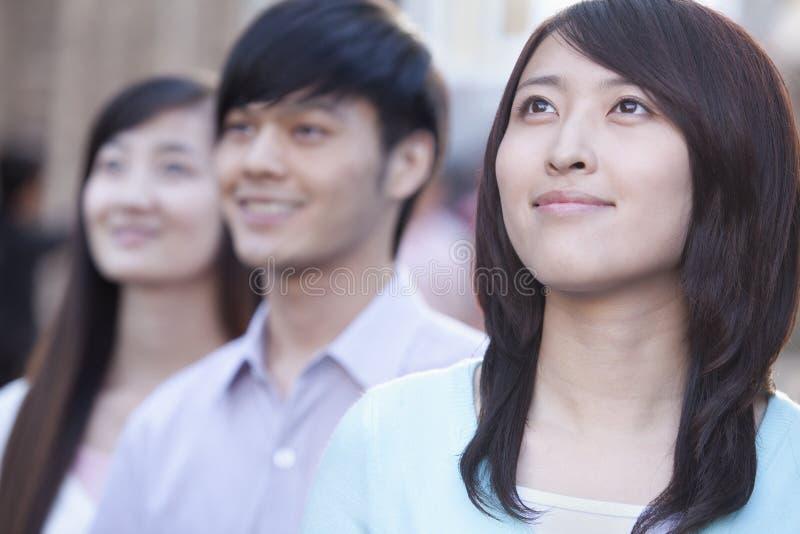 连续站立三的青年人查寻在北京 免版税库存照片