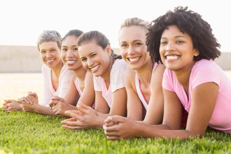 连续说谎微笑的妇女和乳腺癌的佩带的桃红色 免版税库存照片