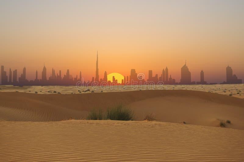 迪拜地平线或城市剪影在从阿拉伯沙漠看的日落 免版税图库摄影