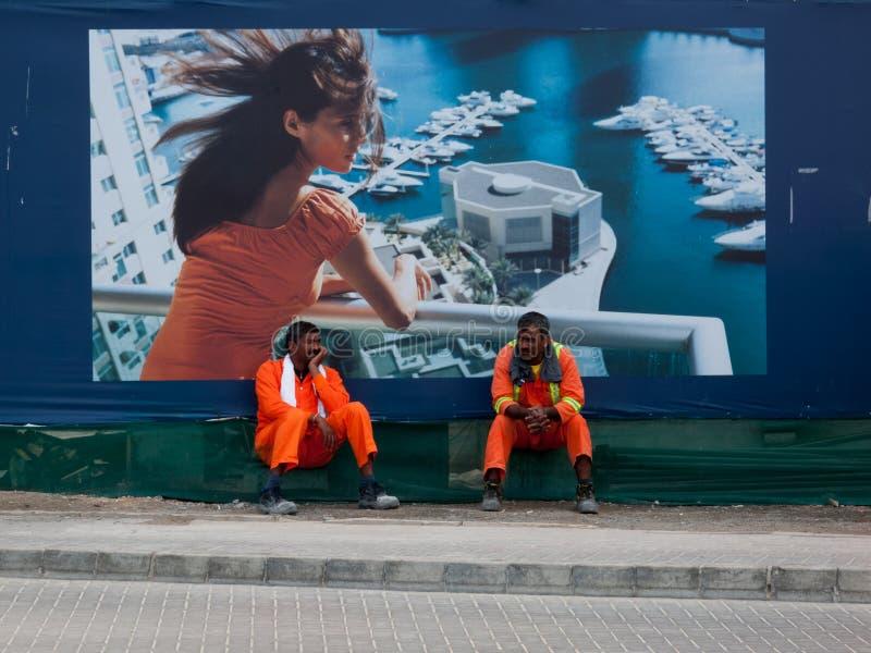 迪拜,阿拉伯联合酋长国- 2017年3月,03:休息在豪华住房前面的两名建筑工人在迪拜小游艇船坞地区签字 免版税库存照片
