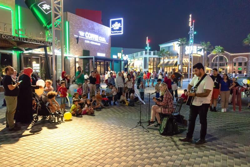 迪拜,阿拉伯联合酋长国- 2017年11月:街道音乐家妇女和人在正方形弹吉他并且唱歌 库存照片