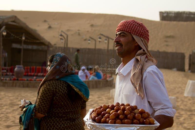 迪拜,阿拉伯联合酋长国- 2012年4月20日:徒步旅行队阵营的职员为准备到达在沙丘打击以后的游人准备食物 免版税库存照片