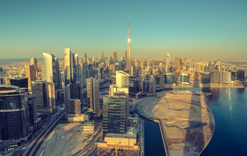 迪拜,阿拉伯联合酋长国- 2015年12月13日:迪拜` s企业海湾风景空中全景视图耸立与Burj哈利法在日落 免版税库存图片
