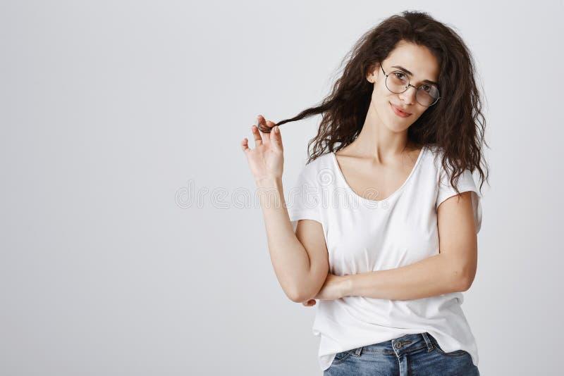 迷人白种人卷发女性使用与头发子线,微笑私秘和好奇地在照相机,佩带 免版税图库摄影