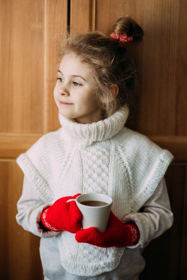 迷人的七岁的女孩喝温暖的茶,站立在窗口旁边 她穿一件温暖的被编织的毛线衣,她 图库摄影
