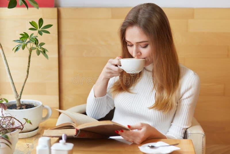 迷人的乐趣喜欢女孩采取饮者茶,读动感十足的书,集中所有注意于剧情 年轻模型在绿色附近坐 免版税库存照片