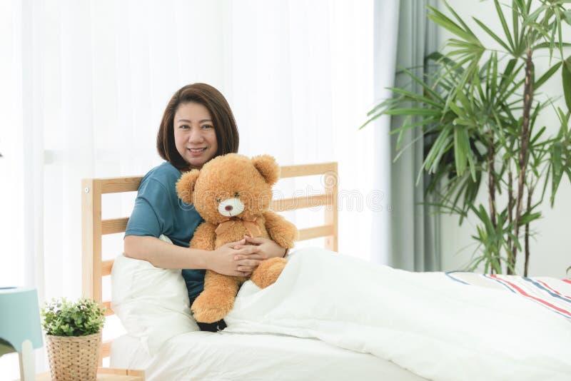 迷人的亚裔妇女在与她的玩具熊的床上 库存照片